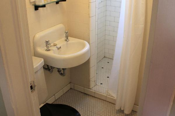 The toilet room features original fixtures, tilework, and step-in shower.