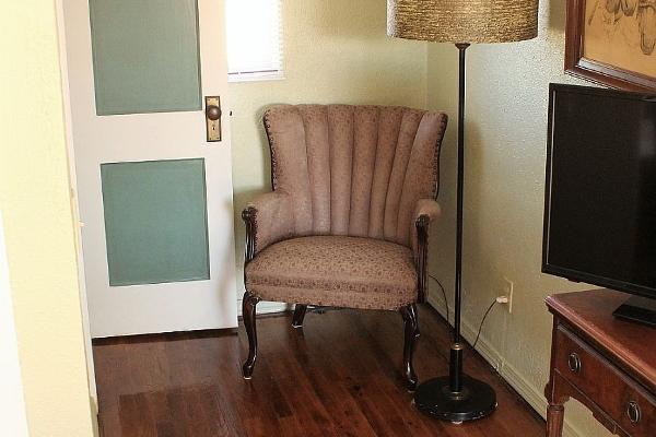 Each queen room has a comfortable area to sit and read or watch TV. Some rooms have original hardwood floors visible, like this one in Room 11.