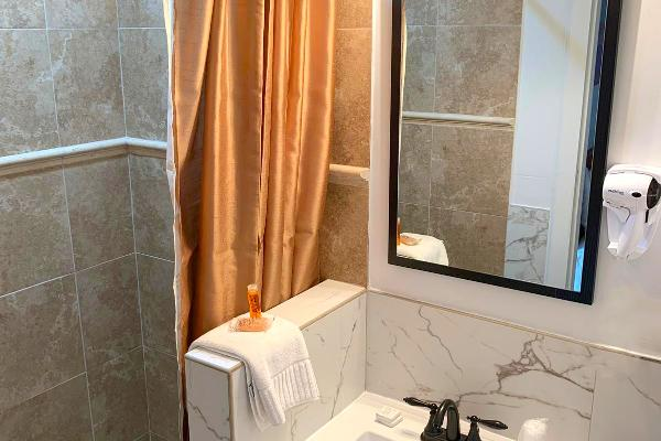 Updated shower with beautiful tile in bathroom.