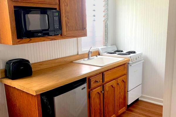 Kitchen with microwave, refrigerator, oven & stove.